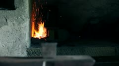 Close up slide shot of the furnace with sparkles and blacksmith takes out the Stock Footage