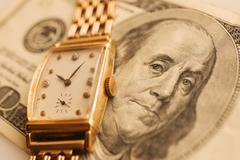Studio shot of banknote and gold watch Stock Photos