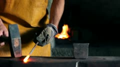 Close up slide shot of blacksmith who shapes hot steal with a hammer Stock Footage