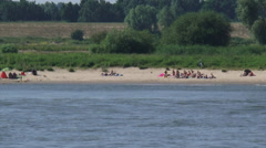 People sunbath at river beach + zoom out river Waal, The Netherlands Stock Footage