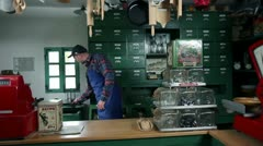 Shot of a young seller who is pouring wine in the glass in an old, retro shop Stock Footage