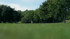 Shot of a coouple that goes on the other golf course carring all the golf Stock Footage