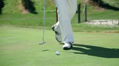 Close up shot on a golfer when hits white golf ball directly to the hall Stock Footage