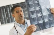 Stock Photo of Male doctor reading MRI scan
