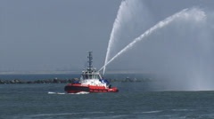 Fireboat greets a ship water with cannons at harbour mouth Stock Footage