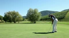 Shot of a man golfer that hits a white golf ball with a golf club and the Stock Footage
