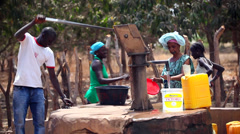 GAMBIA, 08 MARCH 2012: Man pumps water from a water station in Africa - stock footage