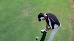 Crane shot of a man golfer that hits a white golf ball with a golf club and the Stock Footage