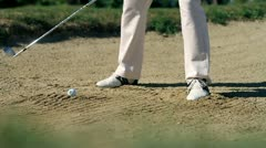 Shot of a man golfer on a sand golf course hitting the white golf ball Stock Footage