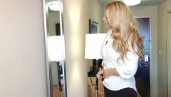 Blond business woman dressing in mirror for work - stock footage