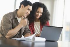Smiling couple planning home ownership with model home - stock photo