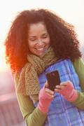 Stock Photo of Portrait of mid adult woman using mobile phone at sunset