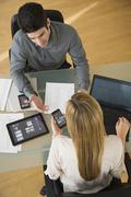 Business man and woman using mobile devices Stock Photos