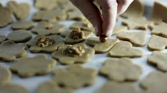 freshly cutted cookies on tray and putting on walnuts - stock footage