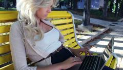 Woman sitting on bench typing in park with laptop, stedicam Stock Footage