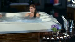 Young couple having conversation and spending night time in jacuzzi on romantic Stock Footage