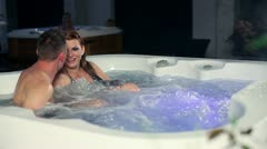 Young couple in jacuzzin having conversation Stock Footage