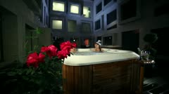 Young couple relaxed in jacuzzi with roses and champagne in the front Stock Footage