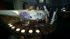 Man prepare glasses and champagne to celebrate with his girlfriend in jacuzzi Stock Footage