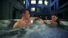 Young couple who spend their romantic time in jacuzzi full of bubbles outside of Stock Footage