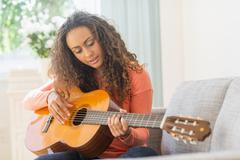 Young woman playing guitar Stock Photos