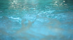 Young couple swimming in pool with waterfall and underwater lights Stock Footage