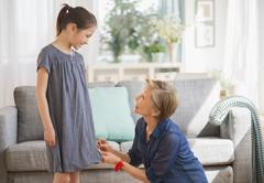 Grandmother attaching sewing pins to granddaughter's (8-9) dress - stock photo