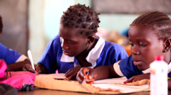GAMBIA, 08 MARCH 2012: Group of yound African students in class working hard Stock Footage