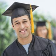 Portrait of male student on graduation ceremony with female student in - stock photo
