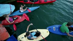 Lots of young people slowly canoeing in lake - stock footage