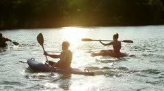 Young people canoeing in the lake at sunset Stock Footage