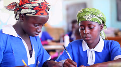 GAMBIA, 08 MARCH 2012:Two young African girls working in class Stock Footage