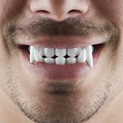 Man wearing fake fangs - stock photo