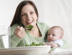 Stock Photo of Mother holding baby and eating
