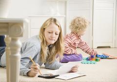 Äiti työskentelee laskimen lapsi leikkii Kuvituskuvat