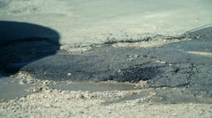 Partly fixed hole in road while car drives over Stock Footage