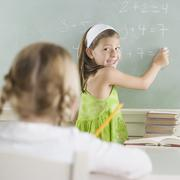 Girl writing on blackboard and smiling Stock Photos
