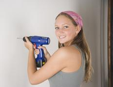 Young woman using cordless drill on wall - stock photo