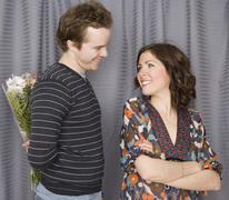 Man surprising girlfriend with flowers - stock photo