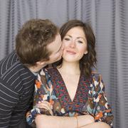 Man kissing girlfriend on cheek - stock photo
