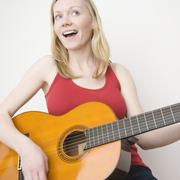 Woman paying acoustic guitar - stock photo