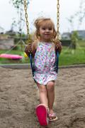 Little girl swinging after a meal Stock Photos