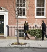 Couple carrying Christmas tree on urban sidewalk Stock Photos
