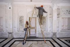 Men at work at the golden temple - stock photo