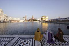Women looks and pray in front of the Golden Temple - stock photo