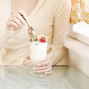 Stock Photo of Woman eating breakfast parfait