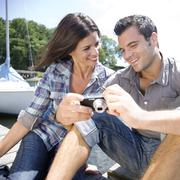 Stock Photo of Couple sitting on dock looking at photos on digital camera