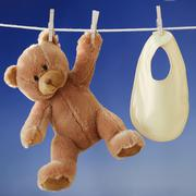 Teddy bear and bib drying on clothesline - stock photo