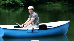 Young man in a boat rowing Stock Footage