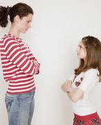 Mother and daughter (10-12 years) having argument, standing face to face - stock photo